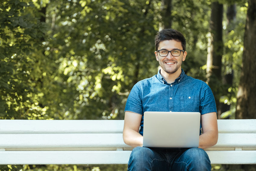 88268438 – young man with notebook sitting on the park bench