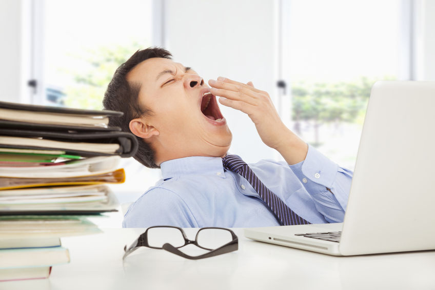 25681934 – exhausted young businessman yawning at work in office