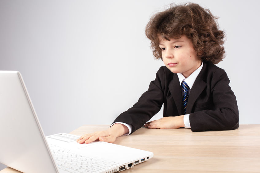 82564595 – little curly-haired businessman with a laptop. gray background.